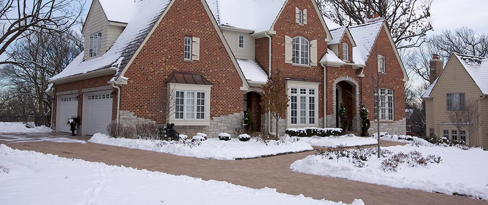 Snow covers a lawn and landscaping in Wauwatosa, WI.