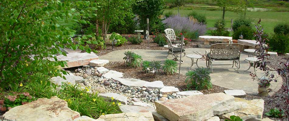Full landscape management around a backyard patio in Hartland, WI.