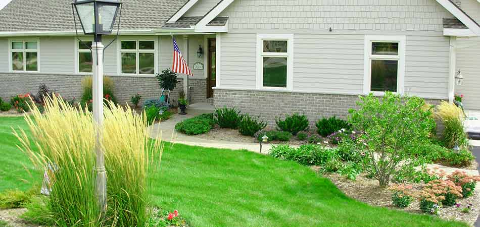 Overseeding has helped this lawn in Pewaukee, WI to become thick and lush.